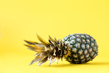 Creative layout made gold pineapple on brightly yellow background.Minimal style.  Tropical Food concept.Summer Idea .Copy space for Text.