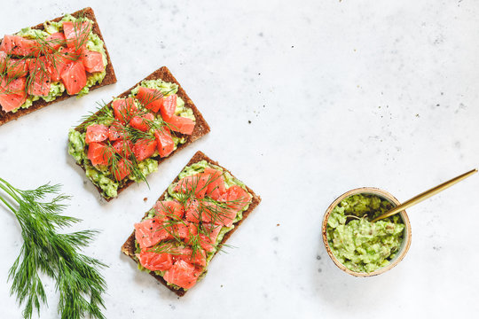 Three toasts with avocado, rye bread, smoked salmon on a white background. Top view, flat lay, copy space.