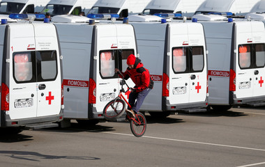A boy rides a bicycle along new Russian-made ambulance vehicles during handover ceremony to hospitals in the southern city of Stavropol