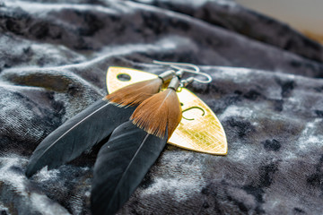 Women's long feather earrings. Brown and black , lie on a Golden label on a gray purple background of velvet fabric. Fashion products