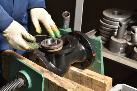 The base for the valve is installed and clamped in a vice for assembly at the factory and the worker installs and fastens the components.