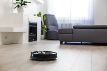 Robotic vacuum cleaner on laminate wood floor in living room