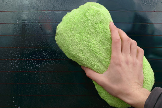 Man washing dirty windshield of car with geen sponge