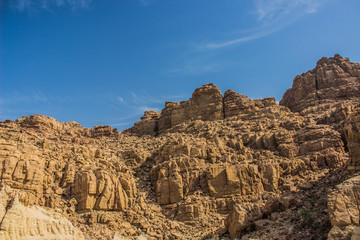 desert bare steep rocks foreshortening from below on vivid blue sky background