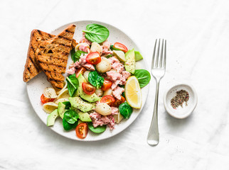 Orecchiette pasta, tuna, avocado, spinach, tomato salad and whole grain bread toast - delicious healthy lunch on a light background, top view