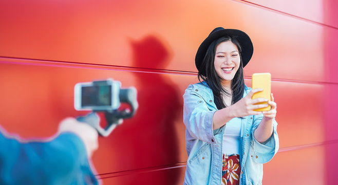 Asian fashion woman vlogging and using mobile smart phone outdoor - Happy Chinese trendy girl having fun making video with gimbal camera - Millennials people, Generation z and technology concept