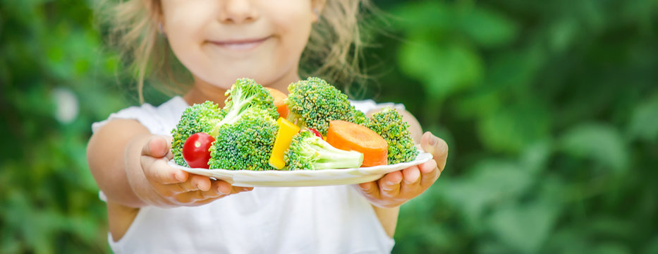 child eats vegetables. Summer photo. Selective focus
