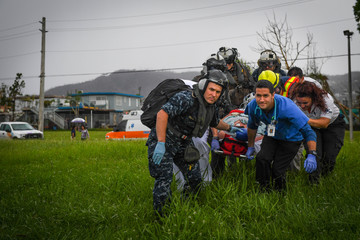 Sailors along with Puerto Rican medical professionals transfer a patient from Menonita Hospital in Caguas, Puerto Rico via an MH-60S Seahawk helicopter
