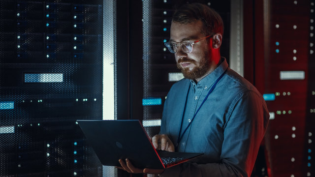 Bearded IT Specialist in Glasses is Working on Laptop in Data Center while Standing Near Server Rack. Running Diagnostics, Doing Maintenance Work. Emergency Red Light from Side Illuminating Specialist