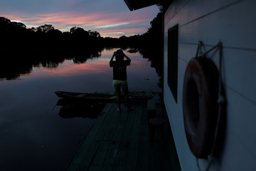 A veterinarian takes a picture of the sunset at the floating research base of Mamiraua institute in the Mamiraua Sustainable Development Reserve in Uarini