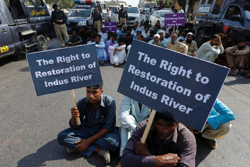Supporters of the Pakistan Fisherfolk Forum hold signs against the proposed construction of all dams on the Indus River, during the last day of long march protest in Karachi