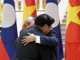 Laos Prime Minister Thongloun Sisoulith (L) and Vietnam's Prime Minister Nguyen Xuan Phuc embrace during their meeting at the Government Office in Hanoi