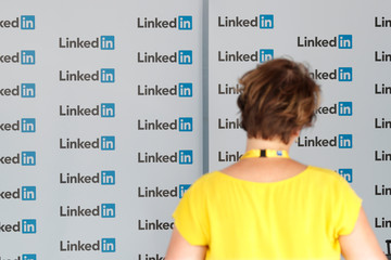 A visitor looks at logos of LinkedIn Corporation at the MEDEF union summer forum on the campus of the HEC School of Management in Jouy-en-Josas, near Paris
