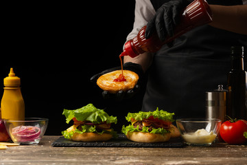 The chef is pouring a cupcake, burger sauce, on the background of the ingredients. Horizontal photo, Tasty and unhealthy food, fast food, homemade recipes, restaurant, catering, recipe book