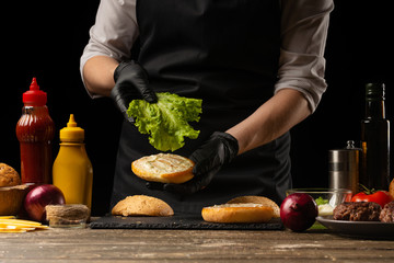The chef puts fresh salad on a burger loaf, with the background ingredients. Delicious and harmful food, fast food, homemade recipes, restaurant, catering, recipe book