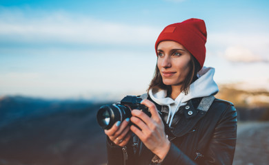 Wall Mural - hipster tourist girl hold in hands take photography click on modern photo camera, photographer look on camera technology, journey landscape vacation concept, sun flare mountain