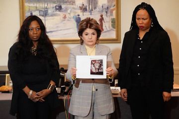 Rochelle Washington, lawyer Gloria Allred and Latresa Scaff hold up a photo as they speak at a press conference to make accusations against singer R. Kelley in the Manhattan borough of New York City