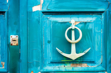 old anchor-shaped door handle on a weathered door
