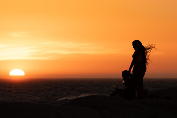 Sunset silhouette: same sex couple of girls at sunset in Camps Bay Tidal Pool, Cape Town, South Africa