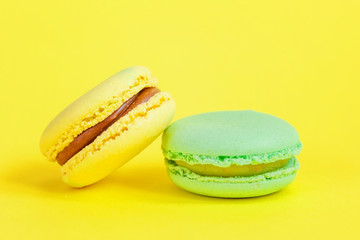 Foto auf Leinwand Macarons Sweet almond colorful unicorn blue yellow macaron or macaroon dessert cake isolated on trendy yellow modern fashion background. French sweet cookie. Minimal food bakery concept. Copy space