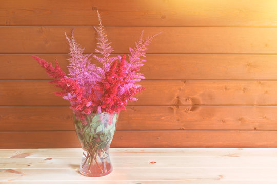 Red and pink beautiful astilbe flowers in glass vase on wooden table.