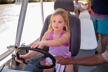 a young girl drives a river boat excursion