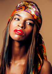 young pretty modern african american girl with bright fashion makeup and shawl on head