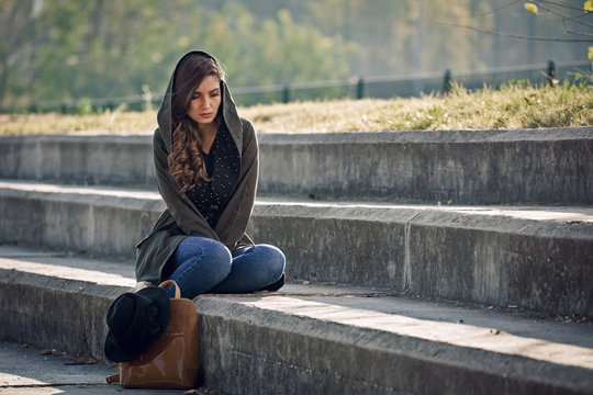 Beautiful unhappy woman sitting alone on staircase outdoors.