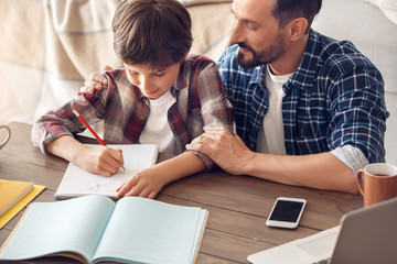 Father and son at home sitting at table dad hugging boy writing homework smiling happy close-up