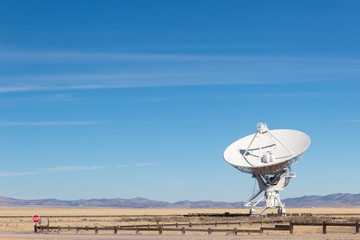 Very Large Array detail of radio antenna against a blue sky and distant mountains, listening to space, horizontal aspect