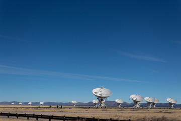 Very Large Array multiple radio antenna dish telescopes against a blue sky in the New Mexico desert near Magdalena, copy space, horizontal aspect Fotoväggar