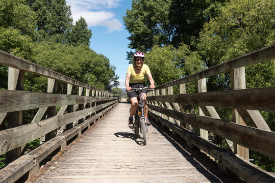 A female, baby boomer cycling crossing a wooden bridge on a Rail Trail near Alexandra, Otago, New Zealand, on a sunny.
