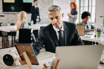 Pensive businessman looking at photo in picture frame at work.