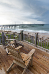 Adirondack chairs overlooking an ocean pier on a North Carolina beach.