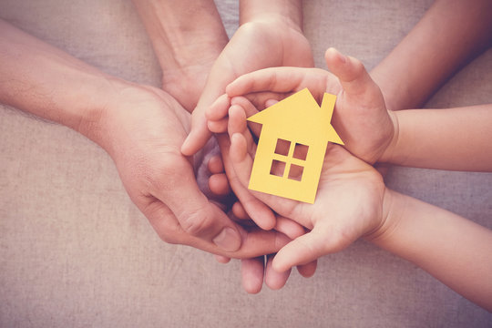 Adult and child hands holding yellow house,  home protection, foster care, family home and homeless shelter, social distancing, stay at home concept