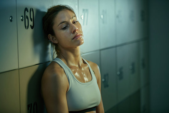 Exhausted athletic woman resting in locker room after sports training.