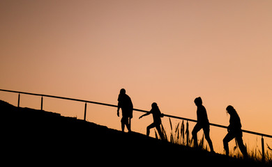 Silhouette image of lovely Caucasian family of four people walking up the hill in twilight evening for recreation and relaxation in weekend day.