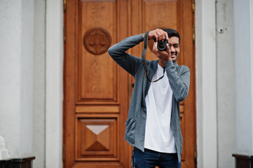 Stylish indian young man photographer wear casual posed outdoor with dslr photo camera at hands.