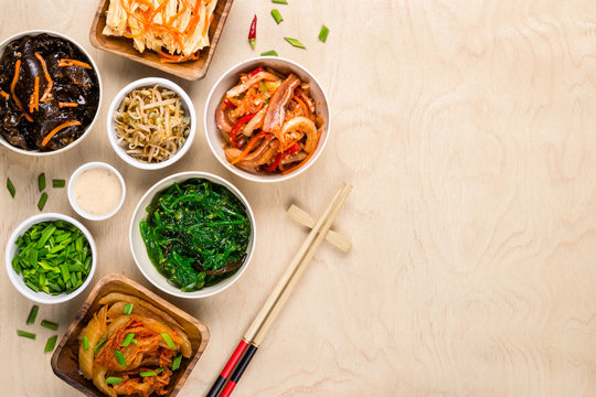 Assorted korean food and chopsticks on wooden background