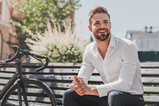 Ready to go. Young smiling man sitting on a bench in the park with a bicycle beside him. Rest and relax concept
