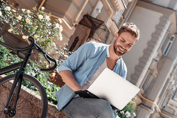 The starting point of all achievement is desire. Young smiling man sitting in the park, holding his laptop. The bike stands beside him. Rest, communication and relax concept