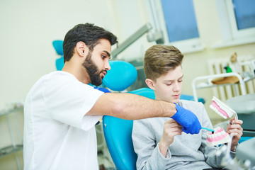 teeth care. Dentist with young patient training to clean