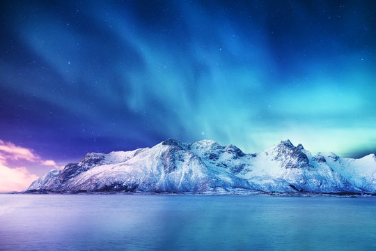 Aurora borealis on the Lofoten islands, Norway. Green northern lights above mountains. Night winter landscape with aurora and reflection on the water surface. Norway-image