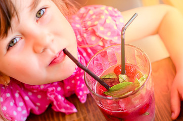 Adorable little girl drinking lemonade with raspberry and basil at table in cosy outdoor cafe.  Happy childhood concept