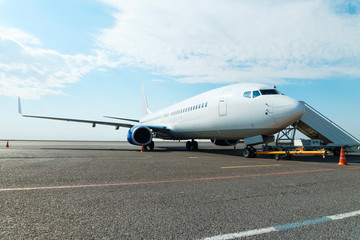 Airplane in the parking lot with fitted passenger gangway at the airport