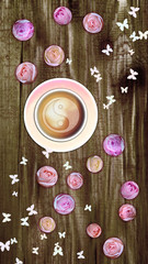 Cup of coffee with little pink roses and butterflies on rough wooden background, digitally generated