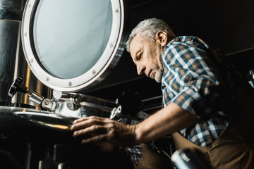 male brewer with grey hair in working overalls checking brewery equipment