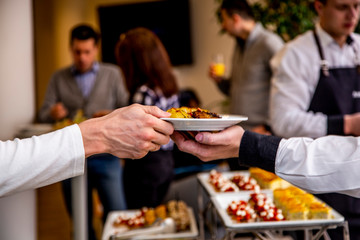waiter's hand passes a plate of potatoes in the hands of a man at catering event on some festive event, party or wedding reception