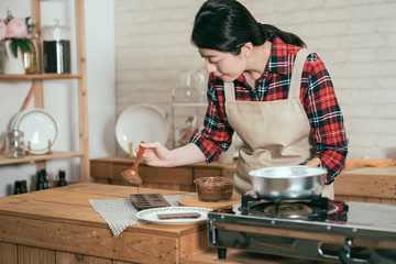 young girl in apron holding spoon pouring melted chocolate into heart shape mold on table in wooden kitchen near stove. woman wearing pinafore handmade cocoa sweet dessert on valentine day.