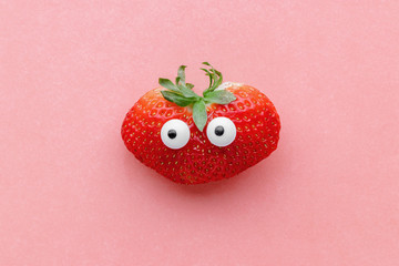 Funny face strawberry on a pink background, creative healthy food concept, top view